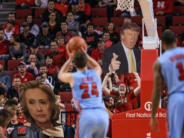 Nebraska basketball fans wave signs with the images of Donald Trump and Hillary Clinton. Nebraska neighbors Iowa, where Clinton and Trump are narrowly ahead days before the caucuses there.
