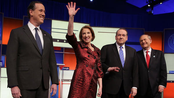 Carly Fiorina waves to the crowd before a GOP debate last week. She's flanked by (from left) Rick Santorum, Mike Huckabee and Jim Gilmore. Several candidates are on dropout watch after Iowa.