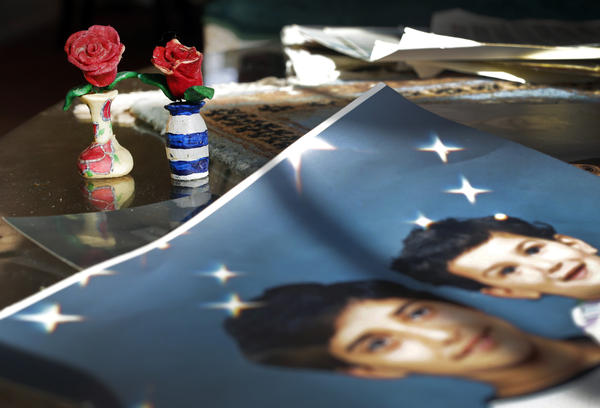 On Dec. 10, 2014, prison artwork created by Adnan Syed sits near family photos in the Baltimore home of his mother, Shamim Syed. Syed, convicted in 2000 of murdering his girlfriend, is appearing at a hearing Wednesday to request a new trial, based on evidence uncovered by the podcast <em>Serial.</em>