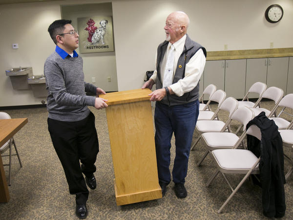 Fernandez helps Mayor John Bechtel move a lectern before a swearing-in ceremony for Fernandez and one other council member, along with a new mayor.
