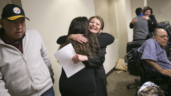 "Wilder, Idaho, Mayor Alicia Mora Almazan (center) receives a congratulatory hug after a swearing-in ceremony at City Hall. At left is City Council member Robert Rivera, and at right is City Council member Guadalupe ""Lupe"" Garcia."