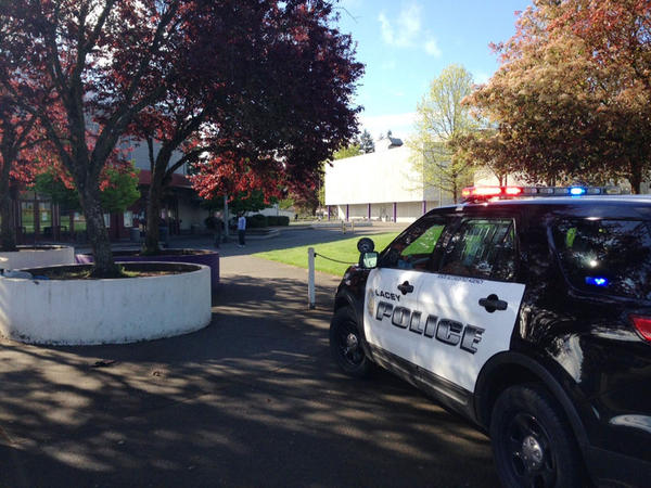 File photo. A Lacey police vehicle sits outside North Thurston High School, the site of a school shooting in April 2015.