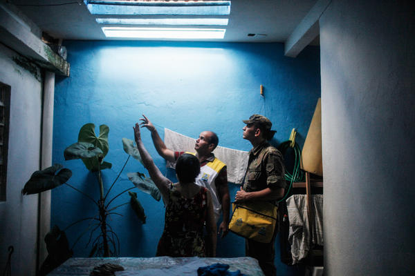 A city health worker and a Brazilian soldier point out potential breeding grounds for mosquitoes in the city of Recife.