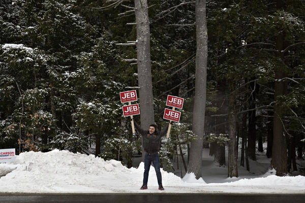 A man holding campaign signs supporting Jeb Bush, former governor of Florida and 2016 Republican presidential candidate, stands along a road near a polling station in Bedford.