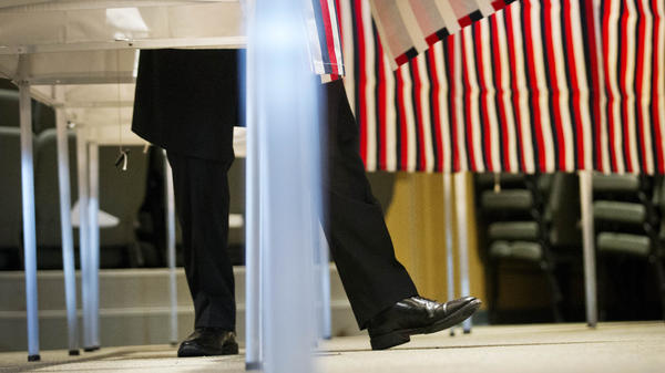 A voter steps out of a voting booth after marking his ballot at a polling site for the New Hampshire primary.