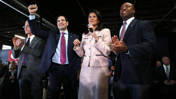 Republican presidential candidate, Sen. Marco Rubio, R-Fla., raises his arm with Gov. Nikki Haley and Sen. Tim Scott, R-S.C., during a town hall Thursday in Greenville, S.C.