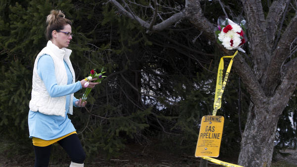 A woman places flowers at a Cracker Barrel restaurant where people were gunned down in the parking lot amid an hours-long shooting spree in Kalamazoo, Mich.