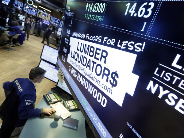 A trader works earlier this month alongside the New York Stock Exchange post where shares of Lumber Liquidators are traded. The company's stock price has been falling ever since a <em>60 Minutes</em> report on the cancer risk from some of its floor products.