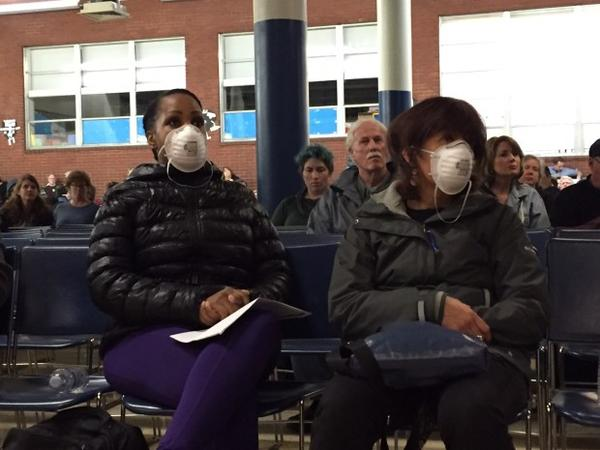 <p>Two concerned residents wore masks to a community meeting about heavy metals detected in the air in Portland.</p>