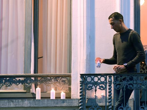 Mohamed Abdeslam places candles on a window ledge of his family's apartment Nov. 18 during a candlelight vigil in Brussels' Molenbeek district town square. Two of his brothers were among the attackers in Paris on Nov. 13.