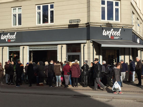 """A crowd waits on the sidewalk for the WeFood grocery store in Copenhagen to open. It's not the first grocer in Europe to sell surplus food. But unlike so-called """"social supermarkets"""" — stores that serve almost exclusively low-income people — WeFood's offerings are very intentionally aimed at the general public."""
