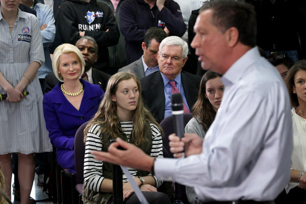Republican presidential candidate John Kasich addresses an audience, including former Speaker of the House Newt Gingrich (second from right) and his wife, Callista Gingrich, during a town hall-style meeting at George Mason University Law School in Fairfax, Va.