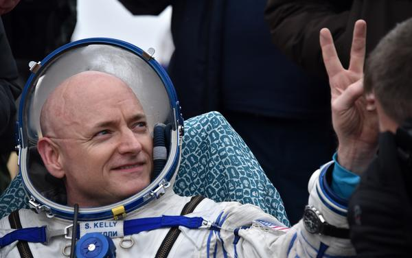 U.S. astronaut Scott Kelly shows a victory sign after landing safely on Earth after nearly a year in space.