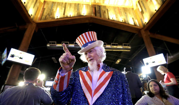 John Evans, dressed as Uncle Sam, waits for Ted Cruz to take the stage during an election night watch party in Stafford, Texas on Tuesday.