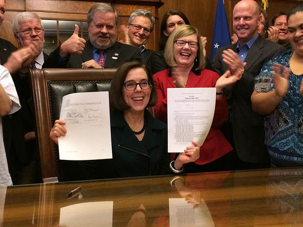 Oregon Governor Kate Brown holds up a bill she just signed. It will raise the state's minimum wage over the next six years.