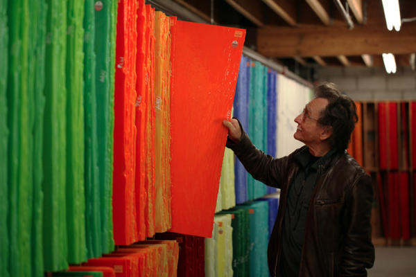 <p>Bullseye Glass co-founder Dan Schwoerer pulls out one of the orange glass sheets his company makes using cadmium.</p>