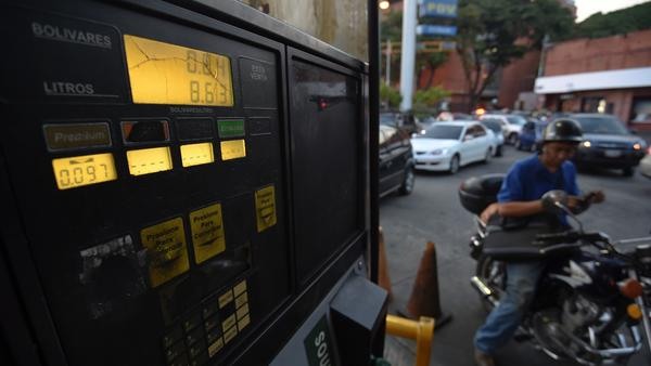 A motorcyclist waits Feb. 17 to buy gas in Caracas, Venezuela. President Nicolas Maduro increased the price of gasoline for the first time in 20 years, as he faced growing pressure to ease an economic crisis in the oil-producing country.