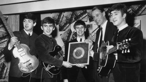 The Beatles in 1963 with their first silver record. (From left) Paul McCartney, George Harrison, Ringo Starr, producer George Martin and John Lennon.