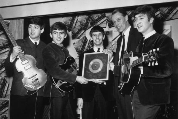 """The Beatles hold their silver disc with record producer George Martin in 1963. Martin, known as the """"Fifth Beatle,"""" died Tuesday at 90."""