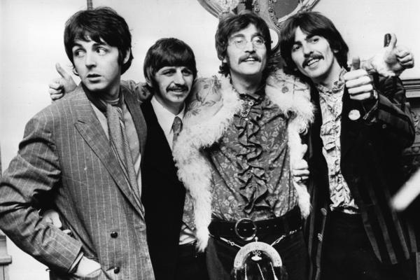 The Beatles celebrate the completion of <em>Sgt. Pepper's Lonely Hearts Club Band </em>in 1967. During the 1960s, Martin was their closest collaborator, producing almost all of the Beatles' music, playing piano with them, writing their orchestral arrangements and figuring out how to turn John Lennon and Paul McCartney's wilder ideas into records.