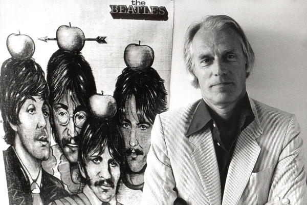 """Martin stands with a Beatles poster in 1984. In a 2011 BBC interview, Martin said: """"They had this wonderful charisma. They made you feel good to be with them. And I thought their music was rubbish."""" Martin signed the Beatles anyway, and came to love their songs."""