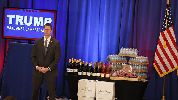 A security agent stands near a display of Trump-branded products that Republican presidential candidate Donald Trump had for guests, including meat, wine and water, before Trump's Tuesday night press conference after the Michigan and Mississippi primaries.