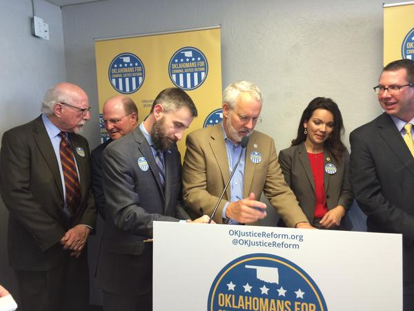 The American Civil Liberties Union's Ryal Kiesel (left) and former Oklahoma Gov. Brad Henry (right) sign initiative petitions for State Questions 780 and 781