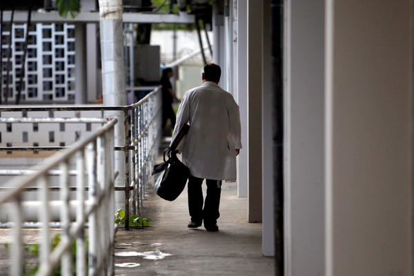 A doctor walks through a hallway at the Centro Medico trauma center in San Juan, Puerto Rico, in 2013. A medical exodus has been taking place for a decade in the Caribbean territory as doctors and nurses flee for the U.S. mainland, seeking higher salaries and better reimbursements from insurers.