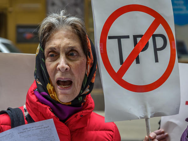 "A protester holds a ""STOP THE TPP"" sign outside the New Zealand consulate in New York, where activists protested the TPP deal."
