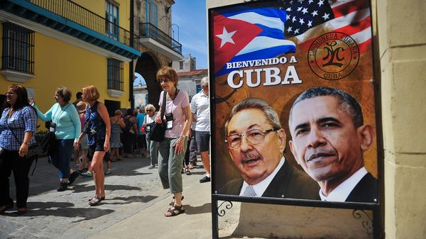 Tourists walk next to a poster of Cuban President Raul Castro and President Obama ahead of the U.S. leader's visit.