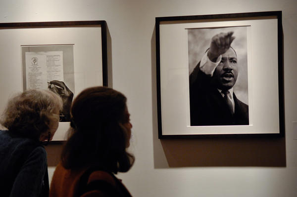 Attendees view Bob Adelman's photography exhibit at the Westwood Gallery in New York City.