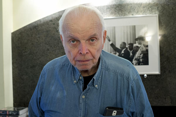Bob Adelman stands in front of a photo of Martin Luther King he made during his days covering the civil rights movement.