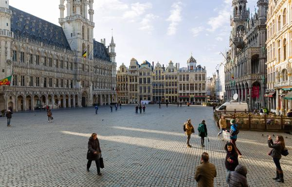 Tourists visit the nearly empty Grand Place in Brussels on Tuesday afternoon, after a string of explosions rocked Brussels airport and a city metro station.