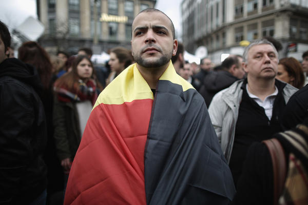 A man wears the Belgian flag as people observe a minute of silence Wednesday at the Place de la Bourse, in honor of the victims of Tuesday's terrorist attacks in Brussels.