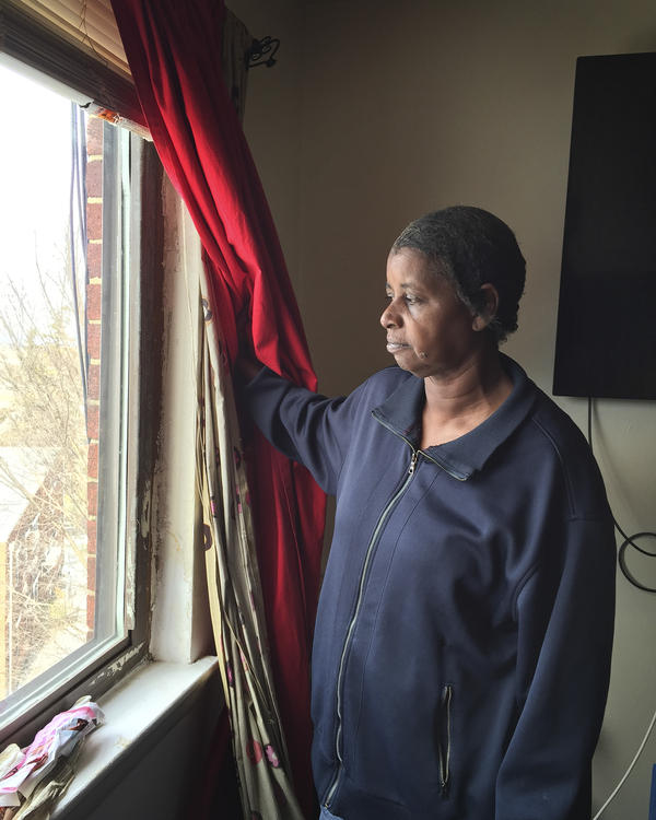 Walker's mother, Patsy Yates, shows where cold air comes in around the window frames.  She says it's so cold sometimes that she boils pots of water on the stove to help warm the apartment.