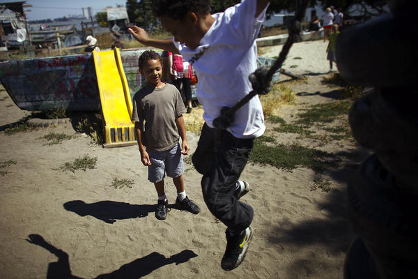 "Deion Jefferson, 10, and Samuel Jefferson, 7, take turns climbing and jumping off a stack of old tires at the Berkeley Adventure Playground in California. The playground is a half-acre park with a junkyard feel where kids are encouraged to ""play wild."""