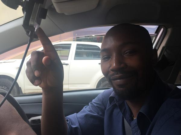 One of Uber's Nairobi drivers, Jackson Kamau, points proudly to an iPhone that shows his high rating.