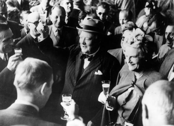 British politician Winston Churchill and his wife, Clementine, make a toast upon their arrival in Switzerland in August 1946. Stories of Churchill's special relationship with alcohol are legendary — and champagne was his truest passion. A new book reveals the extent to which that passion imperiled his already threadbare bank balance.