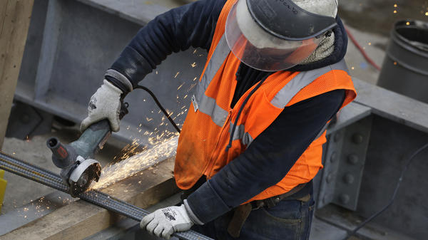 A construction worker uses a grinder to cut through steel reinforcing bars Feb. 1 in New York. A surge of job seekers sent the unemployment rate up 0.1 percentage point, to 5 percent, in March.