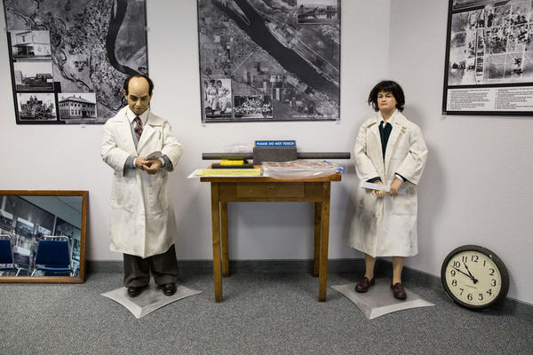 Figures representing Enrico Fermi, left, and Leona (Woods) Marshall Libby, stand in the waiting area of the Manhattan Project B Reactor Tour Headquarters in Richland, Washington, where visitors gather before making the 40-mile drive to the B Reactor.