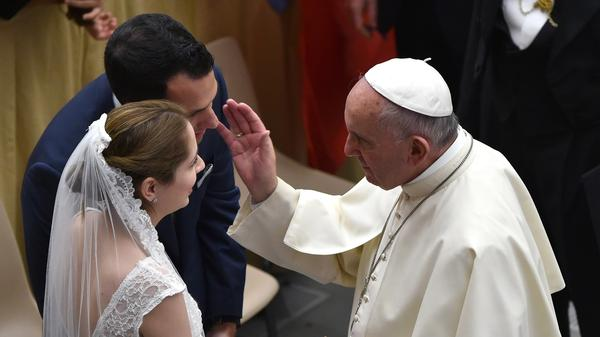 Pope Francis blesses a newlywed couple during his weekly audience in the Paul VI hall in Vatican City on Aug. 12, 2015.