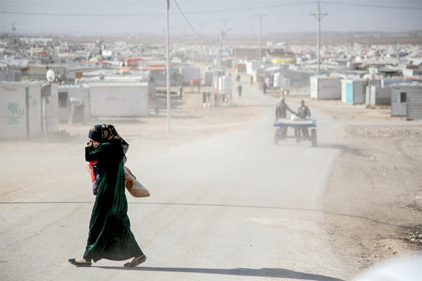 A mother shields her child from the dust in Jordan's Zaatari Camp for Syrian refugees.