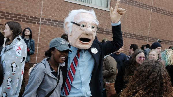 A supporter wearing a Bernie Sanders mask poses with a supporter before a campaign event at Temple University, April 6, 2016, in Philadelphia, Pennsylvania.