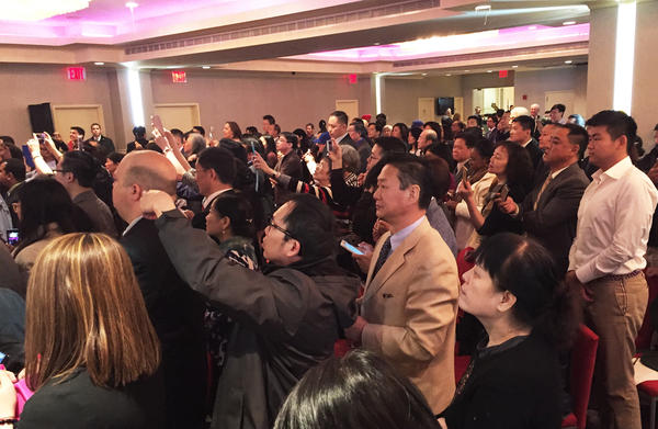 Attendees of a Hillary Clinton campaign rally raise their smartphones to take photos of former President Bill Clinton inside a Chinese banquet hall in Flushing, N.Y.