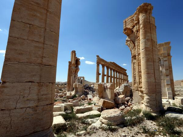 The remains of the Arch of Triumph, shown here in a March 31 photo, stand in the ancient Syrian city of Palmyra, a World Heritage Site. The arch and other monuments were destroyed by ISIS last year.