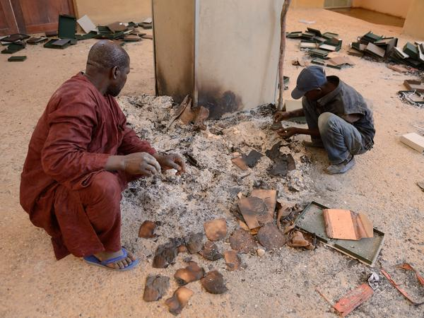 Men recover burned ancient manuscripts at the Ahmed Baba Centre for Documentation and Research in Timbuktu, Mali, on Jan. 29, 2013. Islamists torched the building, which housed thousands of the manuscripts, and destroyed mausoleums and monuments in the city.