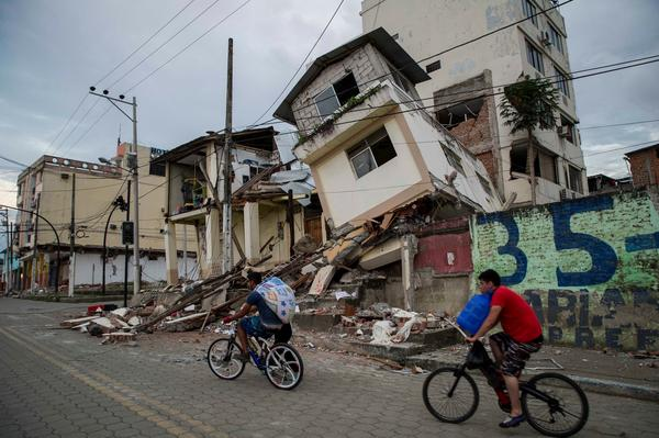 Bicyclists travel past damaged buildings in Pedernales, Ecuador, on Monday. Hundreds of people were killed and thousands wounded in a devastating quake over the weekend.