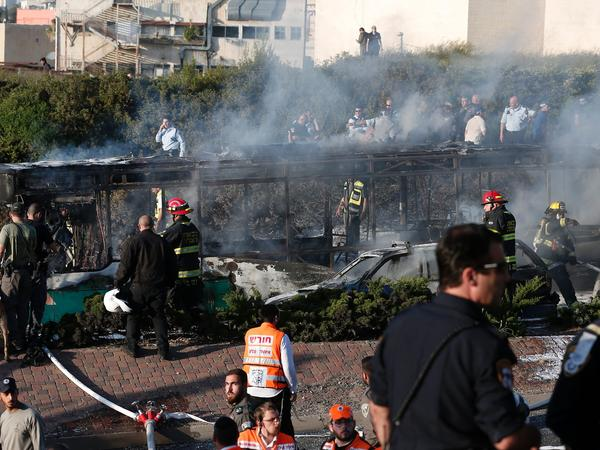 Israeli security forces and emergency services gather around a burned-out bus following the explosion in Jerusalem on Monday.