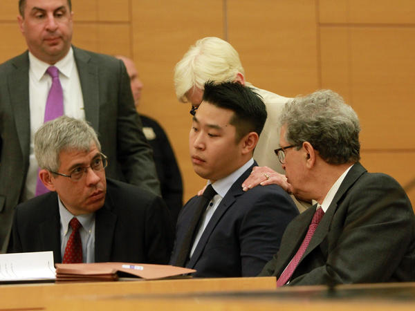 Peter Liang sits with his attorneys for his sentencing at Kings County Supreme Court in Brooklyn, N.Y.