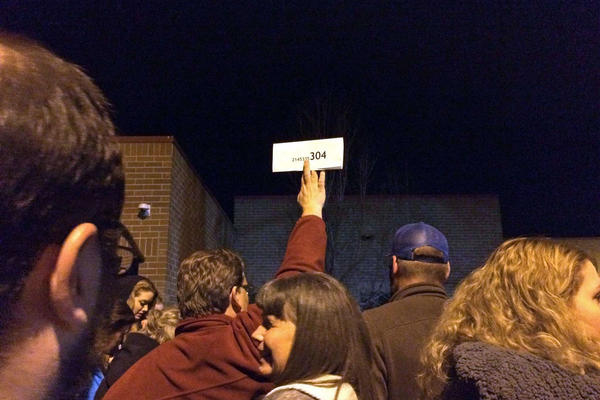 A precinct card is held aloft at Lincoln Middle School in Fort Collins, Colo. The over-capacity crowd caucusing for the Democratic Party was pushed outside for their Super Tuesday polling.